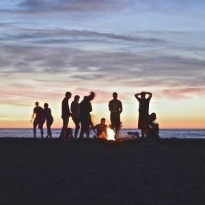 friends on beach at bonfire