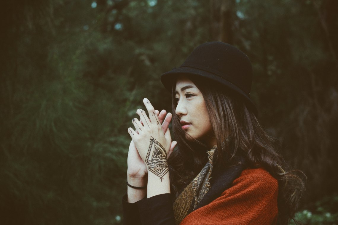 woman in hat with hands clasped