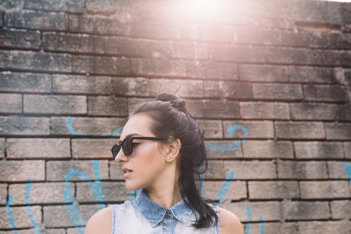 woman standing in front of brick wall