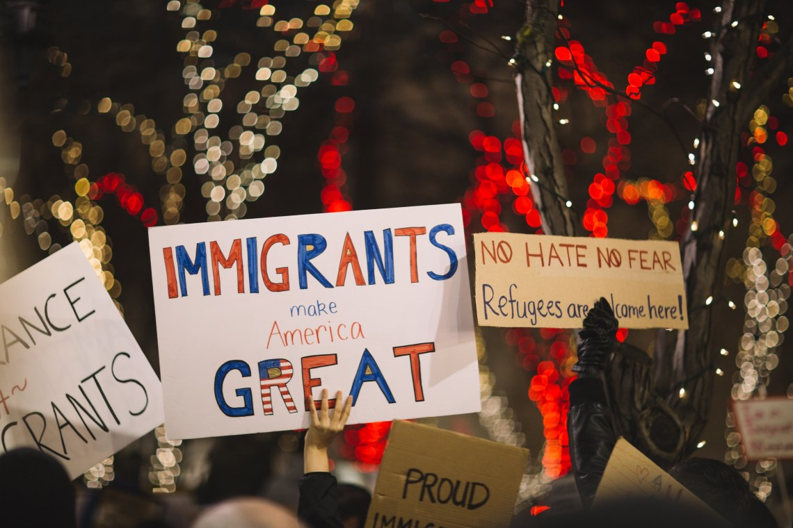 People hold up pro-immigration signs at a protest
