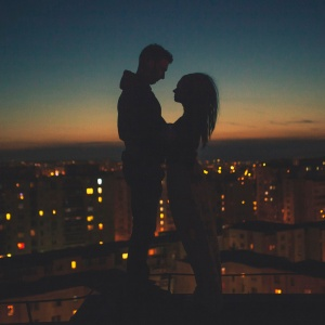 a man and woman embrace in the sunset over the city