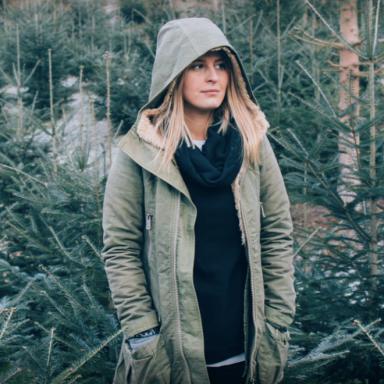Girl standing amongst fir trees