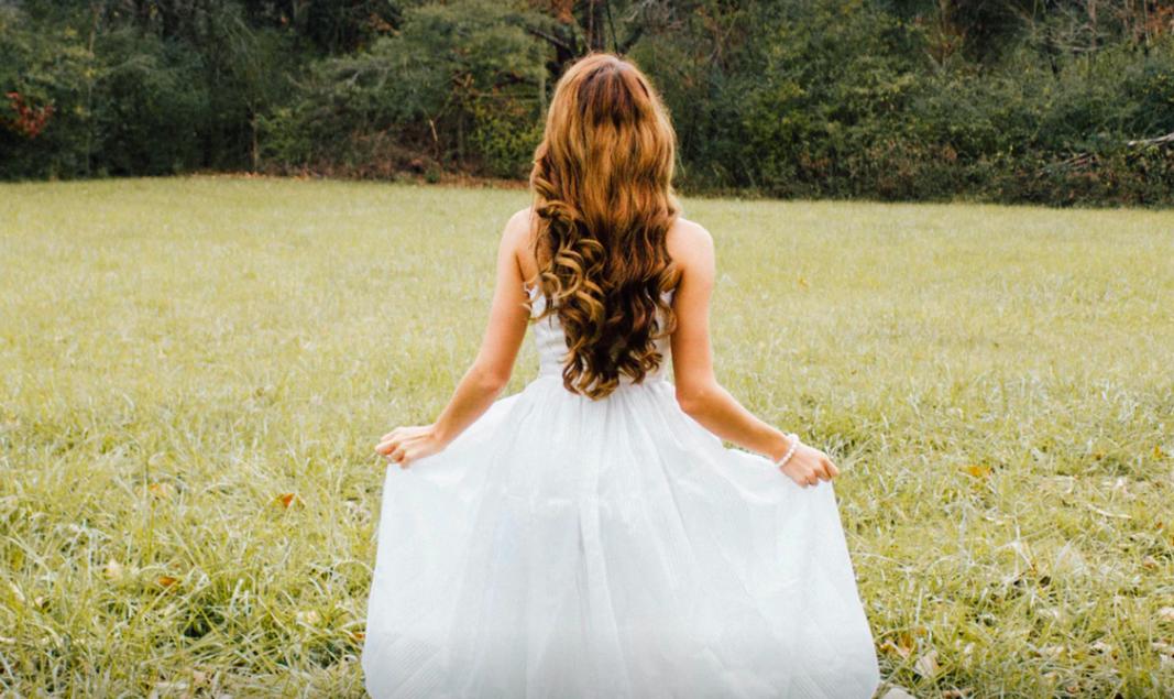 Girl in white dress in green field