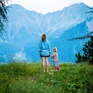 a mother and a daughter standing in front of a mountain