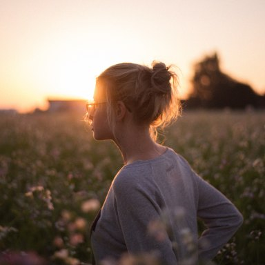 Blonde woman standing in front of sunset