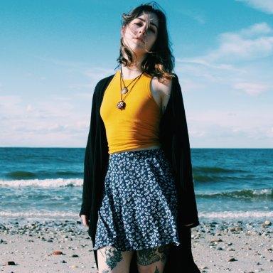 Girl in skirt standing on beach