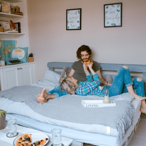 couple on bed eating pizza