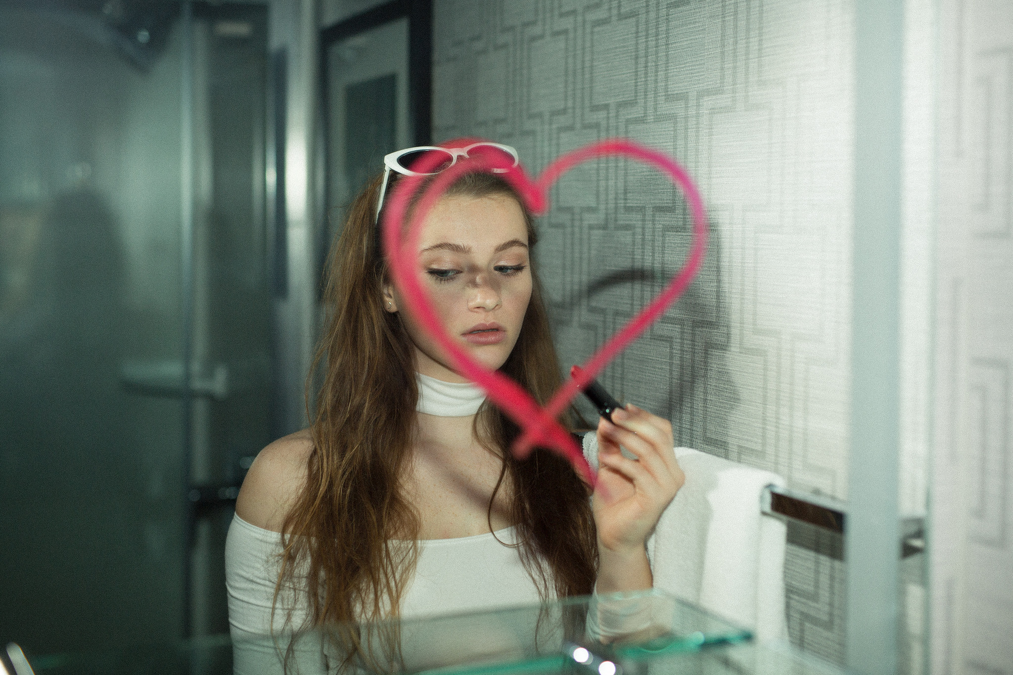 pink lipstick on mirror with girl's reflection