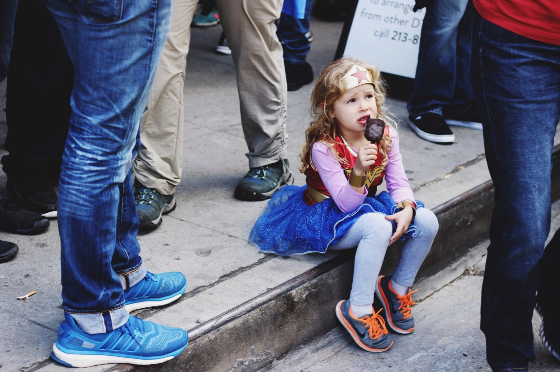 little girl sits on a street in a wonder woman costume