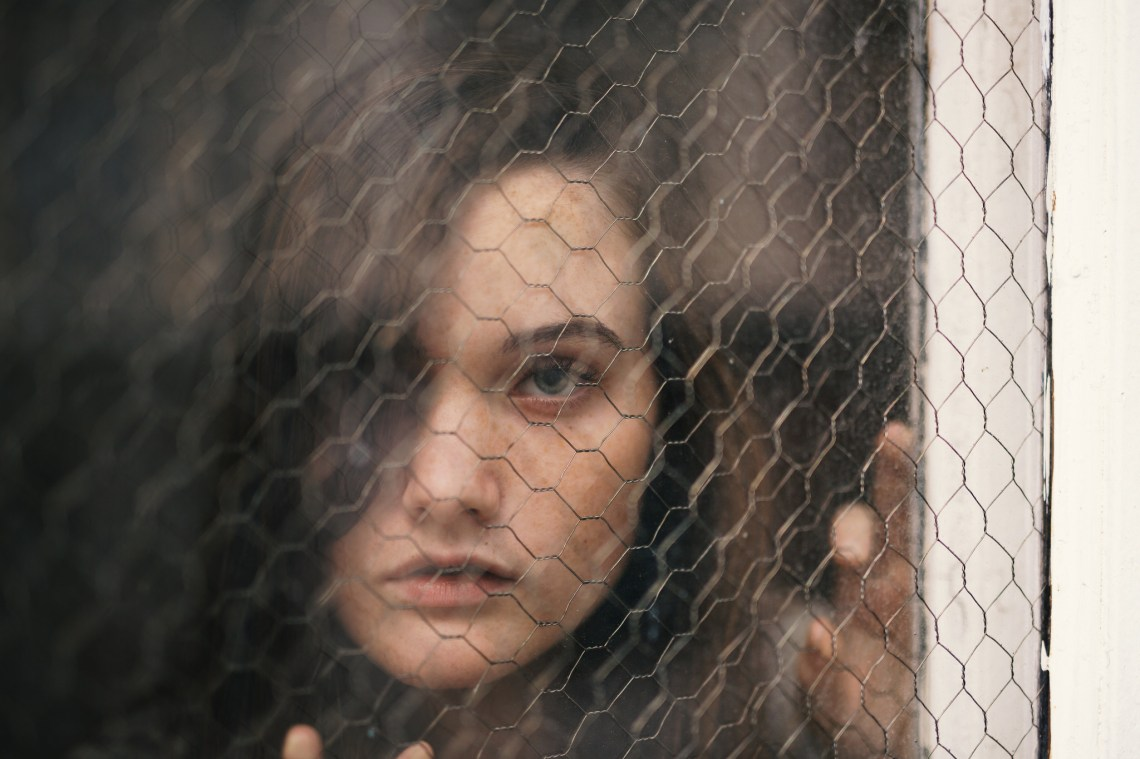 Woman stares out from behind a wire fence, looking isolated