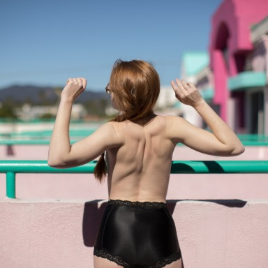 Woman stands topless on a balcony and stretches