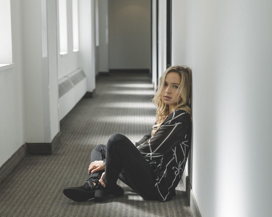 blonde woman dressed in black sitting on floor