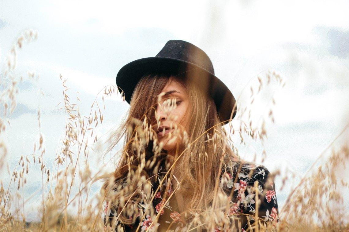 Woman in fedora in field