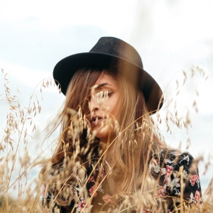 Woman in fedora in field