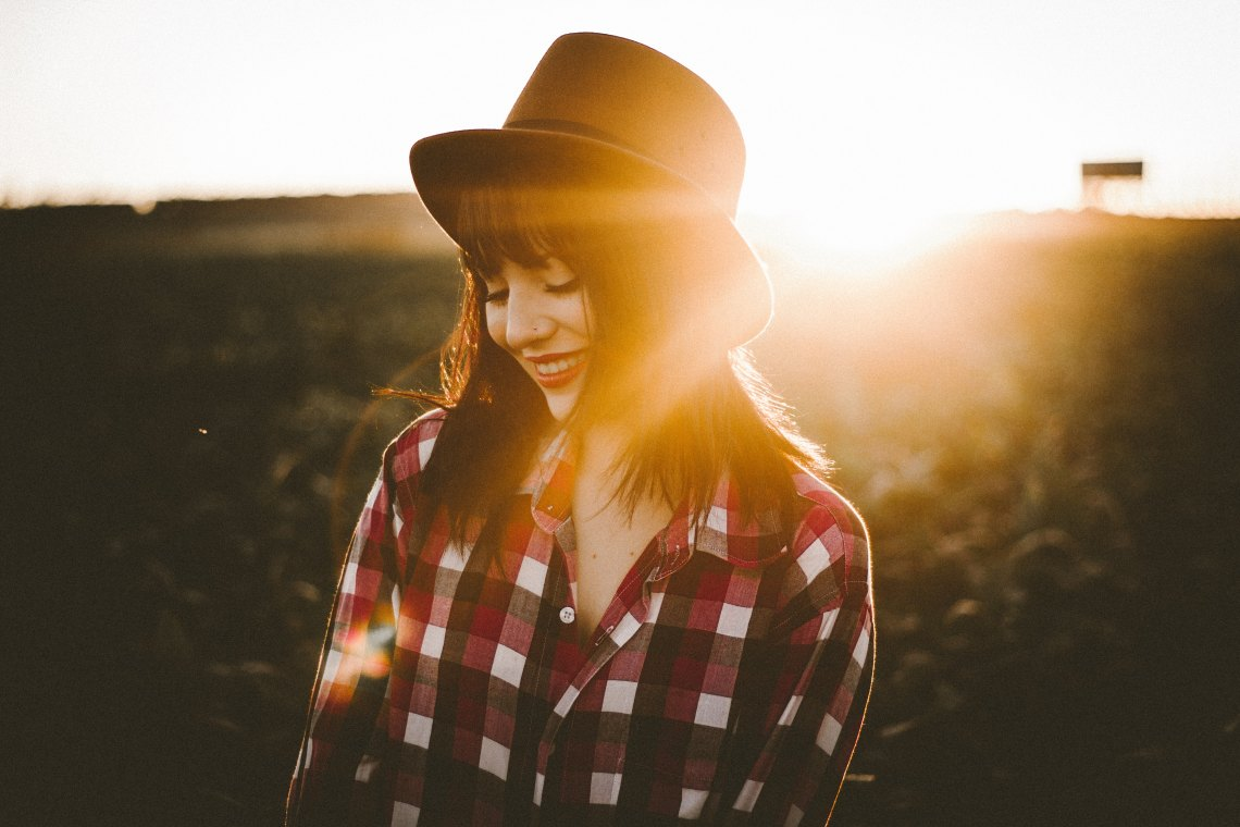 Woman wearing fedora and plaid shirt
