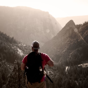Man hikes in the mountains looking adventurous