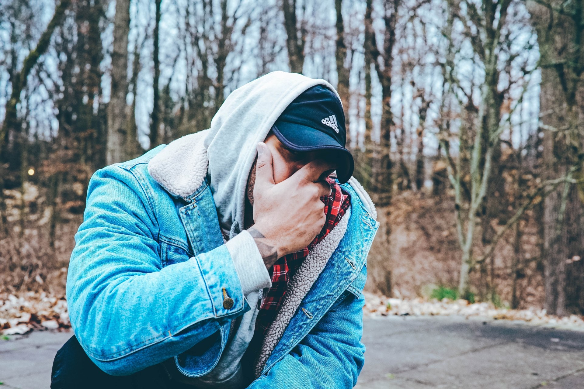 guy in jean jacket covering his face