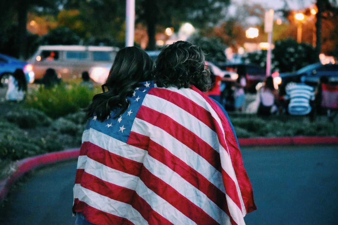 Two women stand with an American flag draped over their shoulders in solidarity