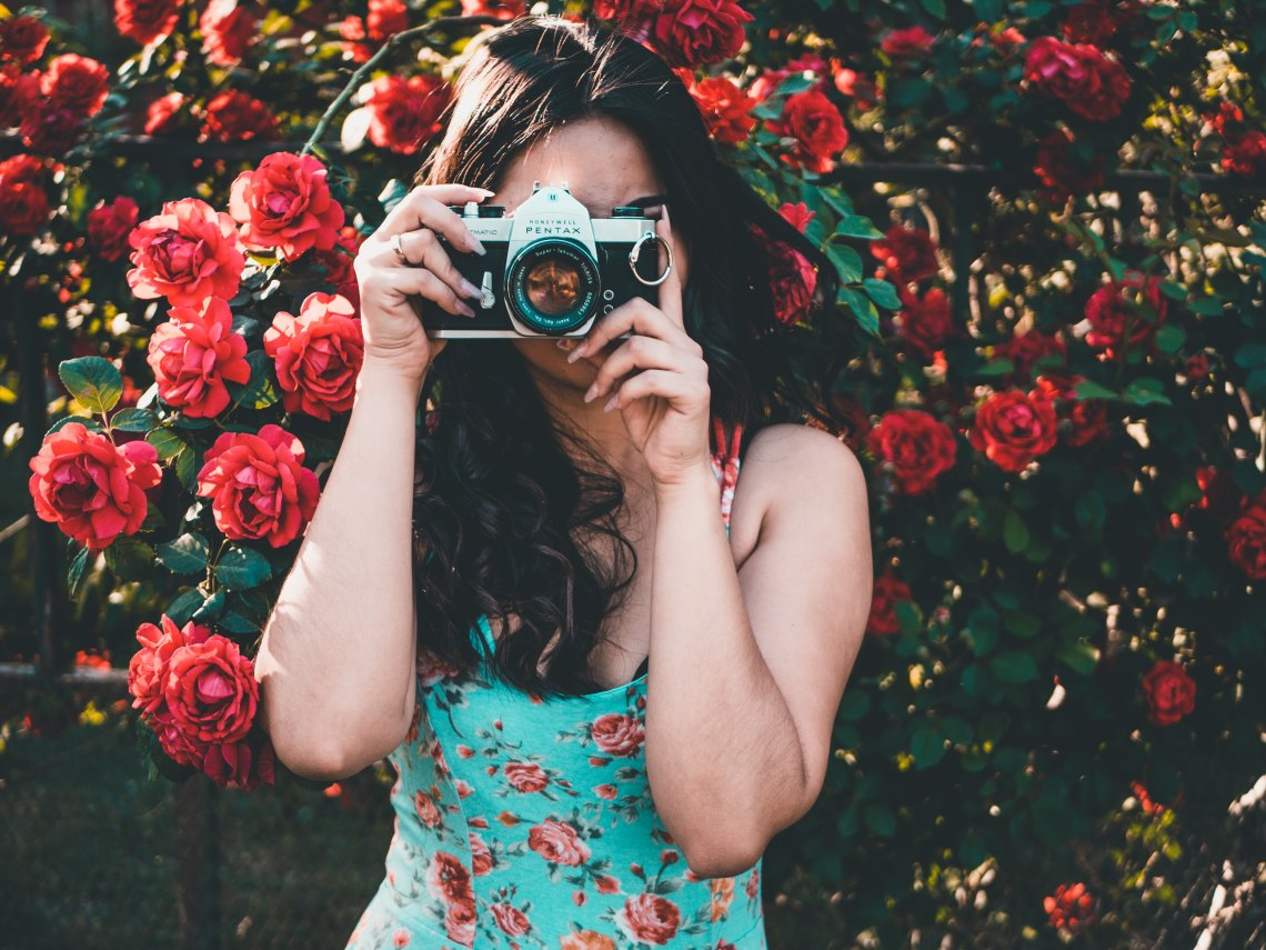 girl in flowers with camera, happy girl, endless possibilities