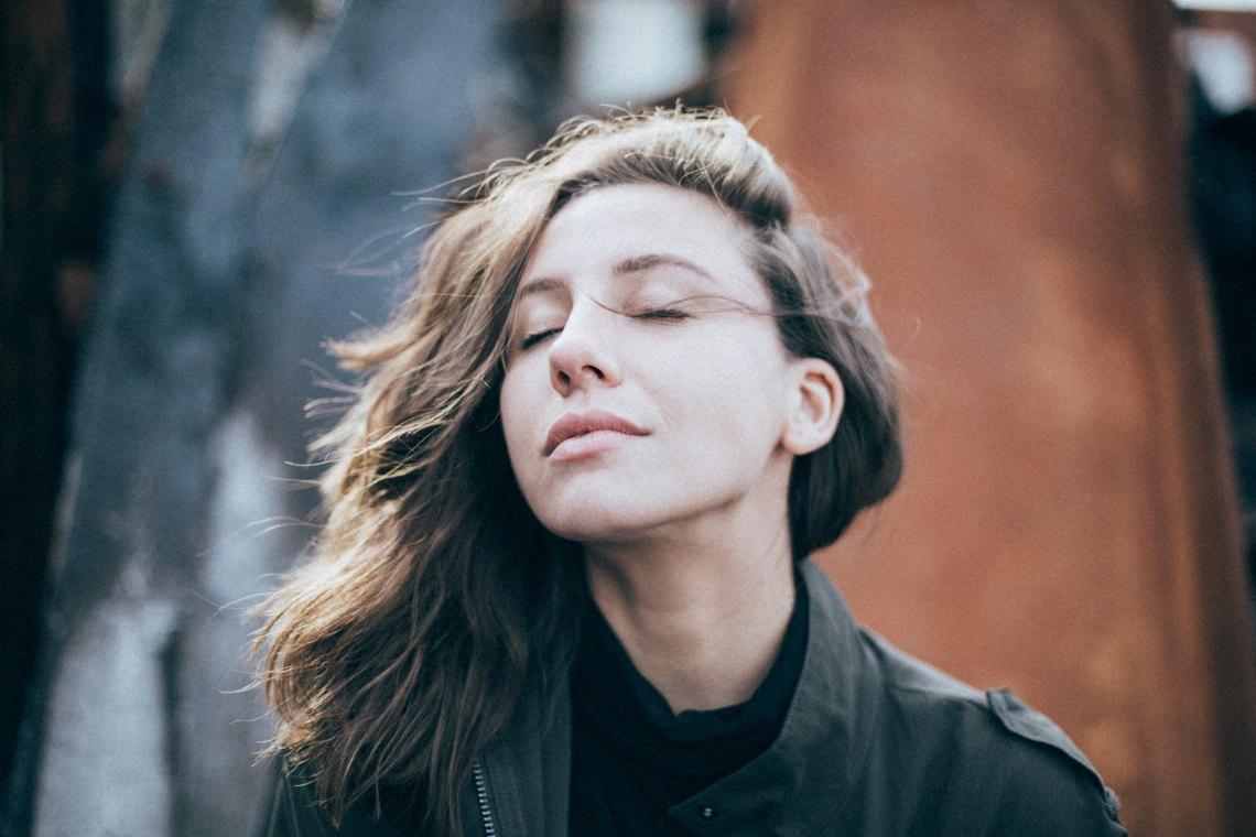 Woman closing eyes and looking at sun