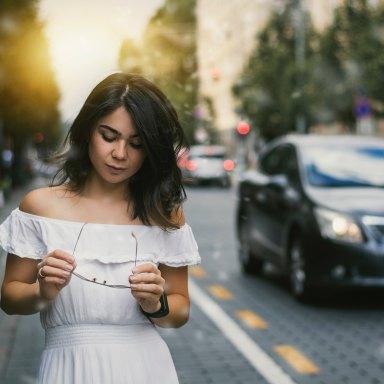 Woman in white dress walking in city