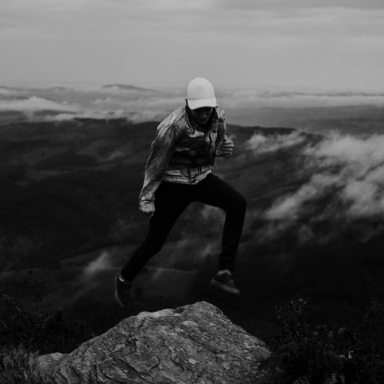 person jumping across mountains, ambition, believe in ambition