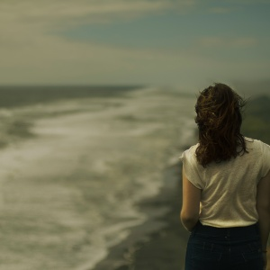 Woman stands staring at the darkened sky and ocean