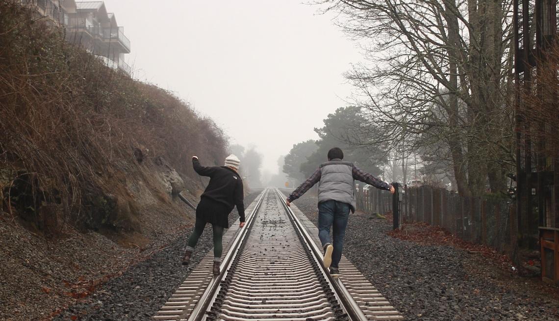 couple walking along train tracks, happy couple, can't fix you