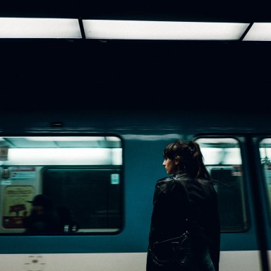 woman stands at a train station looking out