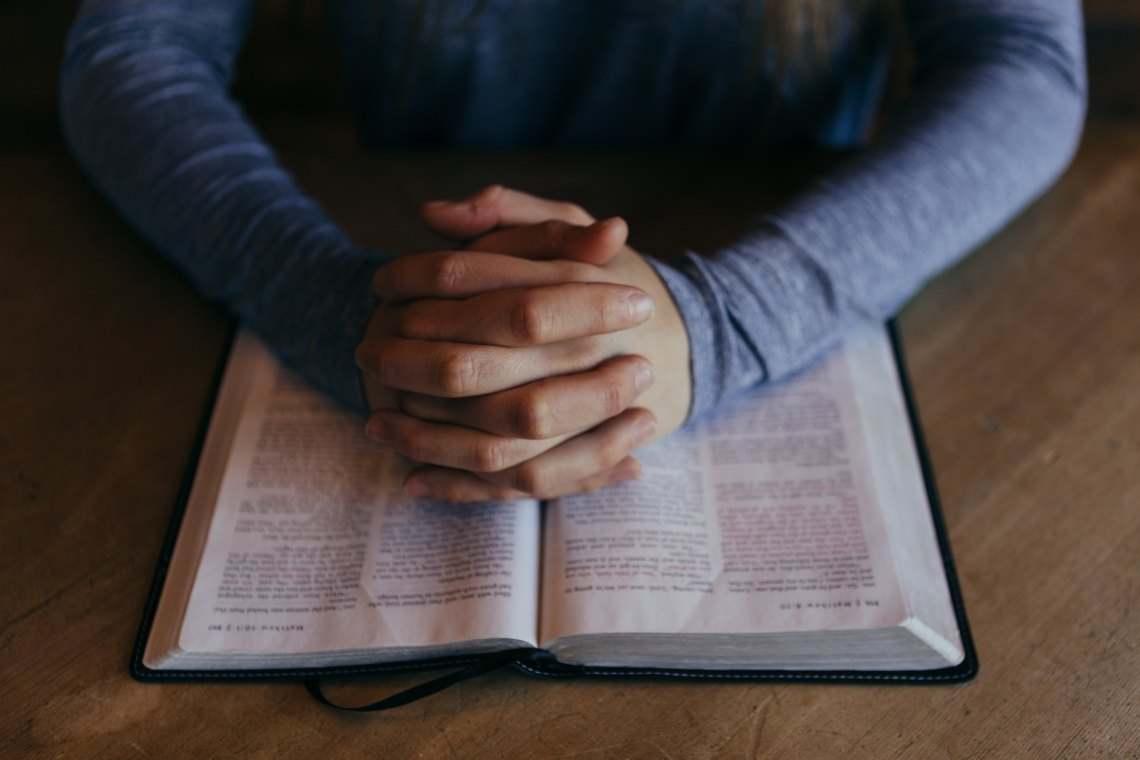 person praying over a bible