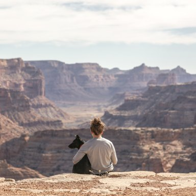 Woman and dog sitting in front of canyon