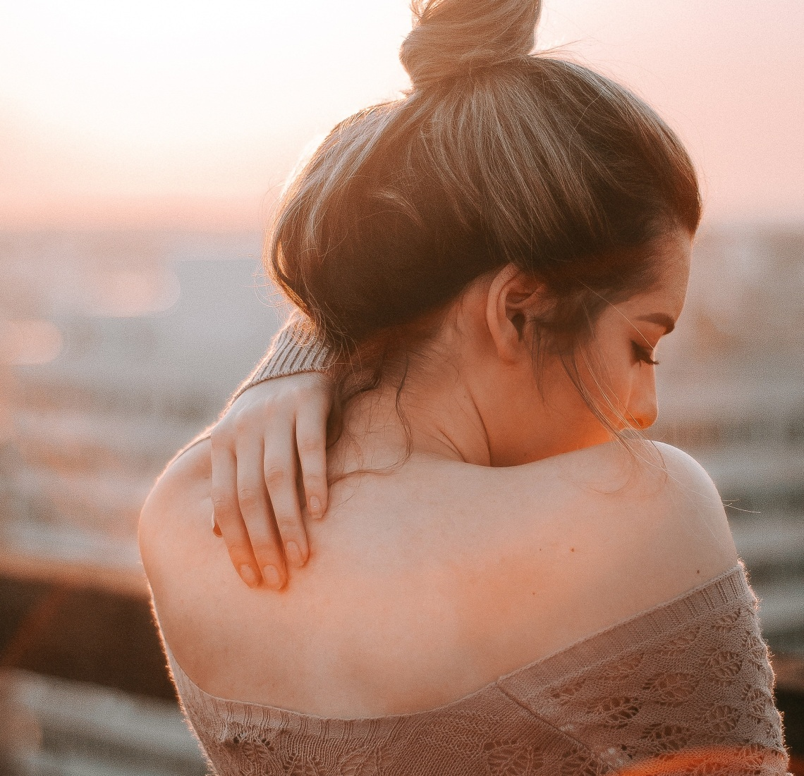 girl with hand on her back, girl in sunset, finding joy