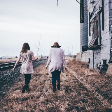 Friends holding hands by railroad track