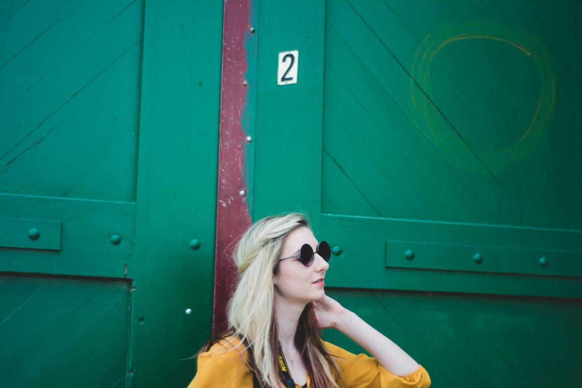 Blonde woman in front of blue door