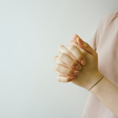 A woman wears a pink sweater for breast cancer awareness