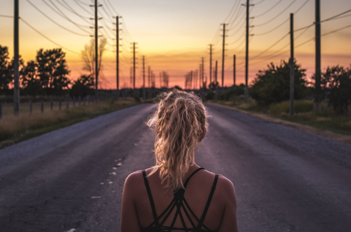 girl at a crossroads, girl looking at road, trusting the road ahead