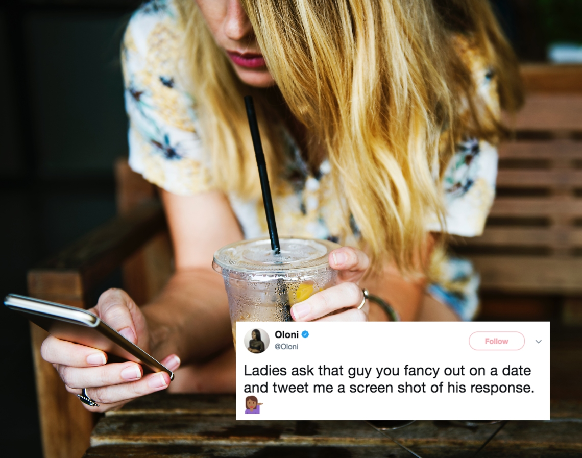 woman looks at her phone while drinking iced coffee