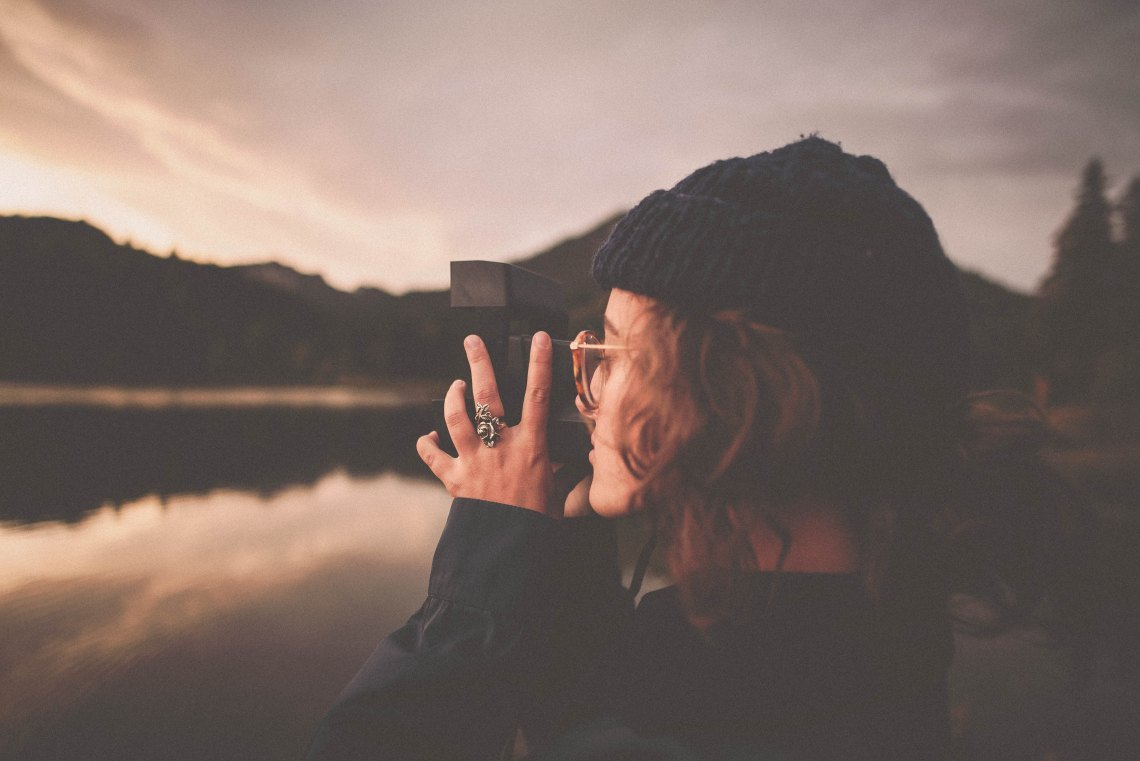 Female photographer looking over lake