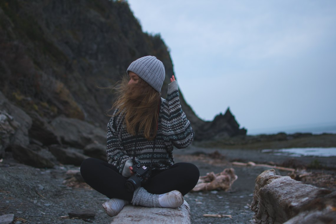 girl sitting by rocks, quotes about gratitude, being thankful