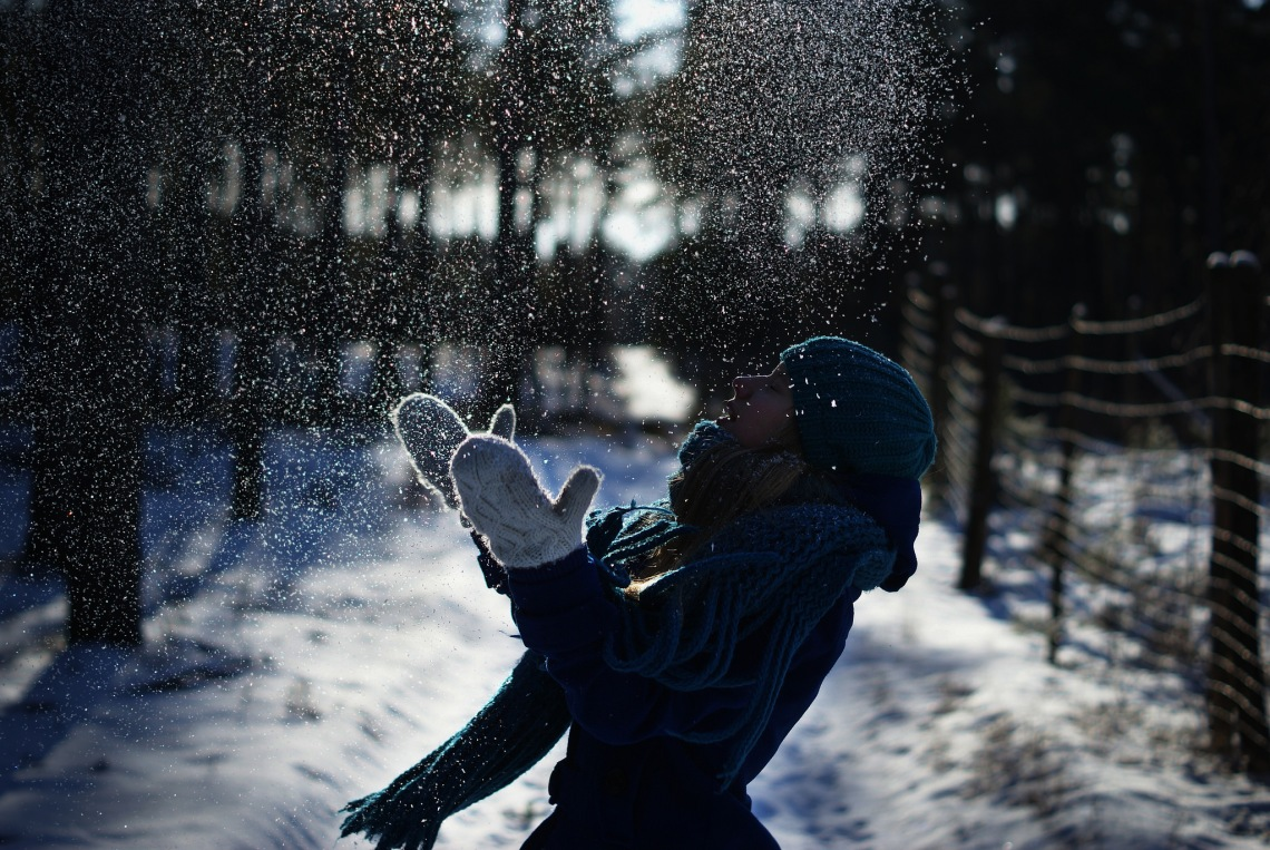 A girl bundled up in winter clothes happily plays with snow while standing on a snowy path