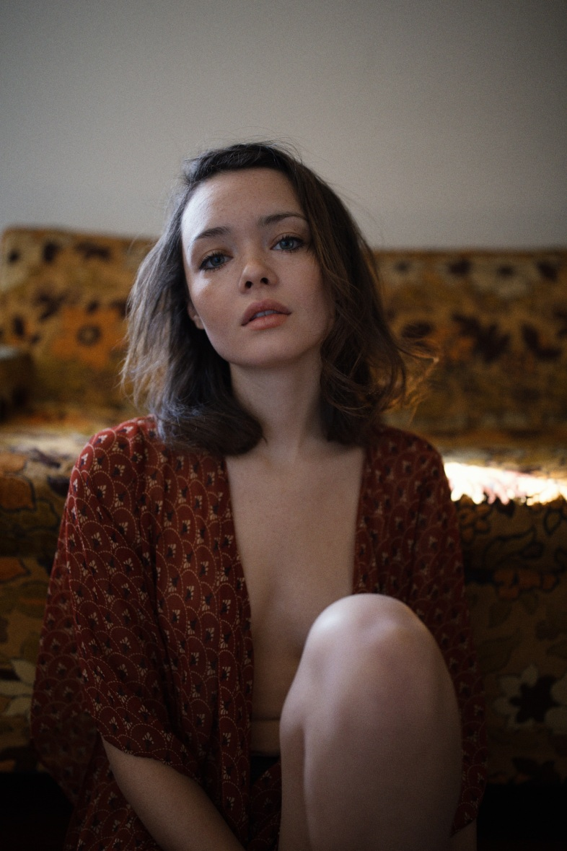 girl sitting staring at the camera open shirt