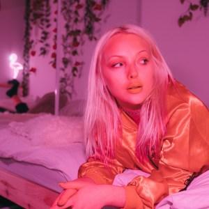 girl lying on a bed pink lighting