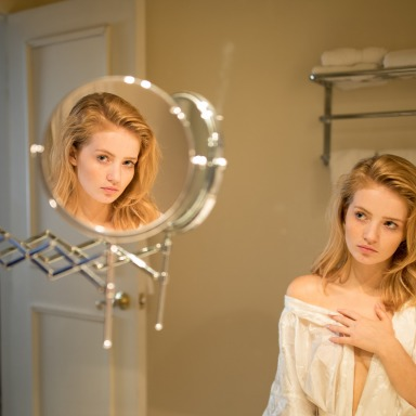 A woman in a white robe looks at herself in a mirror; her reflection stares at the camera