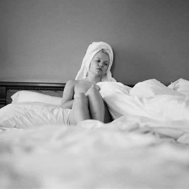 A woman sits in bed half-naked while being surrounded by blankets