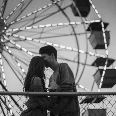 couple in front of a ferris wheel