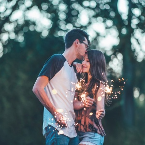 A man and a woman holding sparklers as the man kissing the woman's forehead