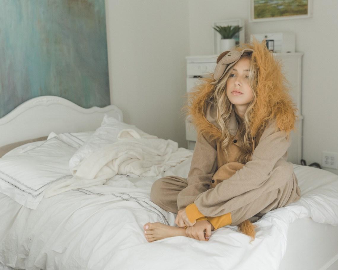 girl in lion onesie sitting on bed