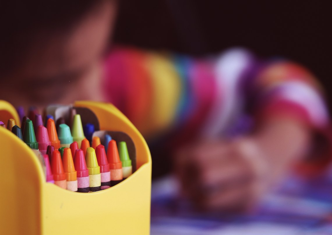 A little girl colors with crayons