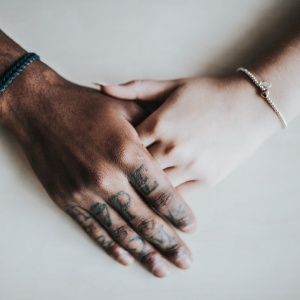 A black man and a white woman hold hands