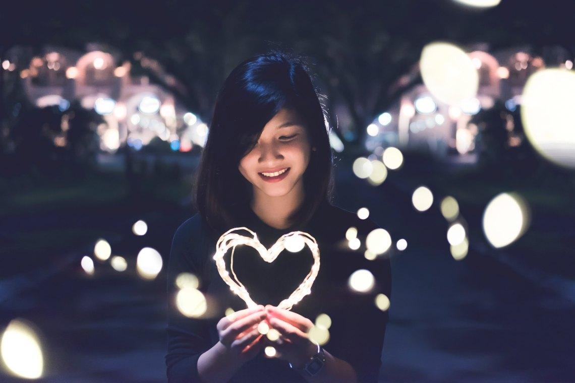 Woman holding heart-shape light